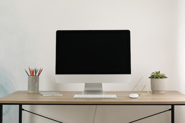 Workplace with computer, tablet and plant on wood table, space for text