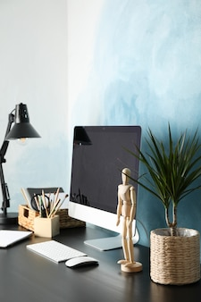 Workplace with computer, wooden man and plant on black wood table, copy space