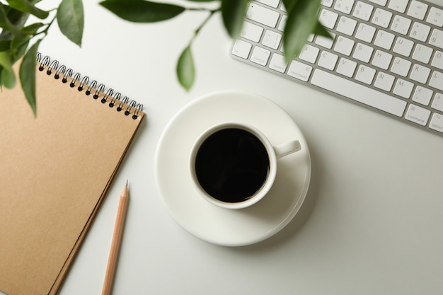 Workplace with cup of coffee on white background