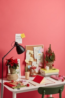 Workplace with decorated christmas tree, eggnog drink in glass, different notes with future plans and motivation phrases, isolated on pink background