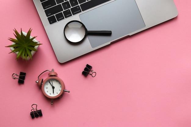 ノートパソコンの目覚まし時計工場と虫眼鏡のある職場ビジネスフリーランス教育の概念
