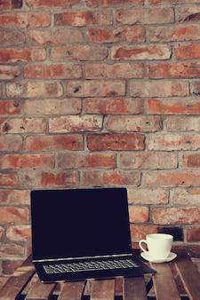 ラップトップとコーヒーカップのある職場