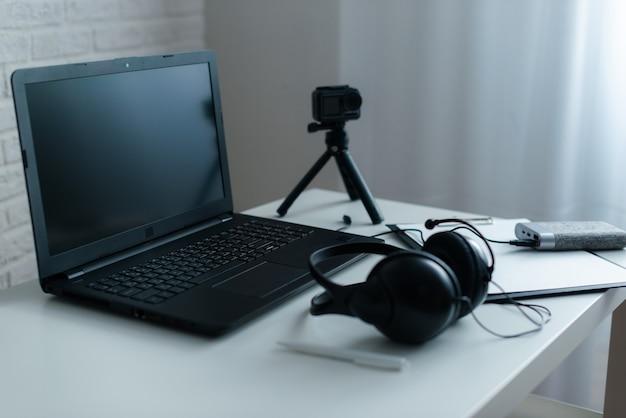 白い机の上にラップトップとヘッドフォンで職場 Premium写真