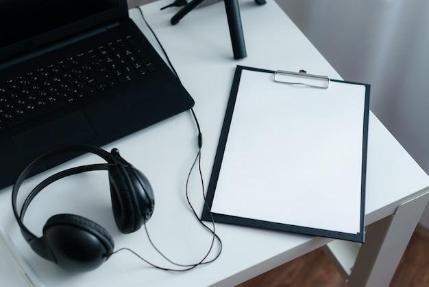 白い机の上にラップトップとヘッドフォンで職場