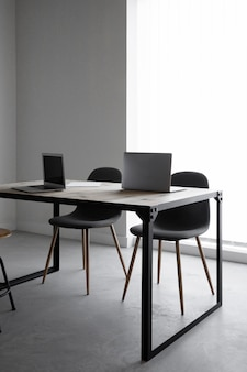 Workplace with laptop and chairs