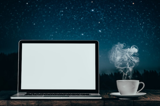 Workplace with laptop and coffee on the night sky