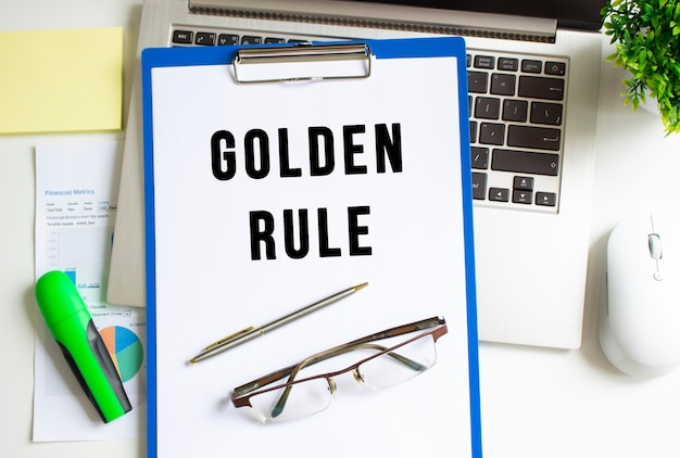 Workplace with laptop, folder and graph on the table. the folder with the text golden rule.