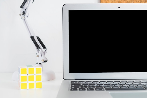Workplace with laptop and rubik's cube