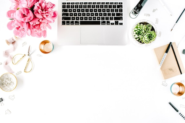Workplace with laptop succulent peonies golden scissors spool with beige ribbon pencils and diary flat lay composition for blog top view