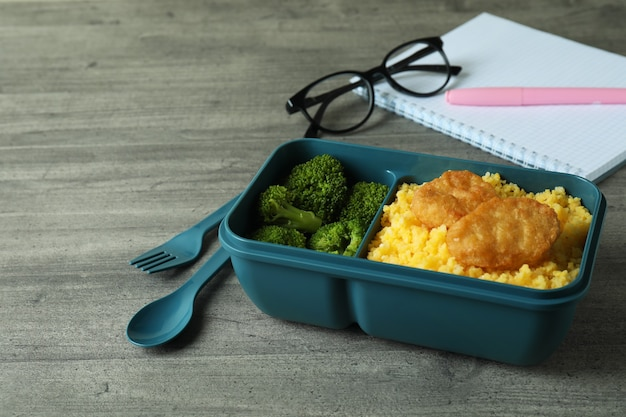 Workplace with lunch box on gray textured table