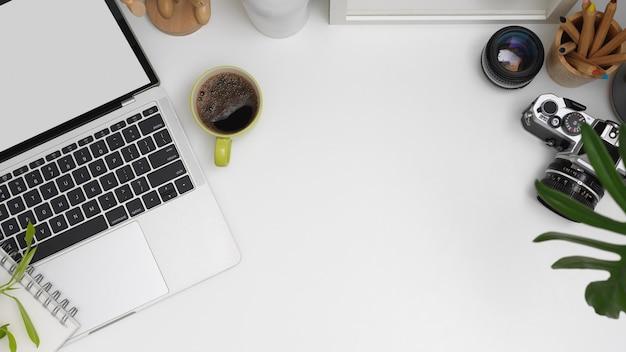 ラップトップ、カメラ、文房具、装飾、白いテーブルにコピースペースを模擬した職場