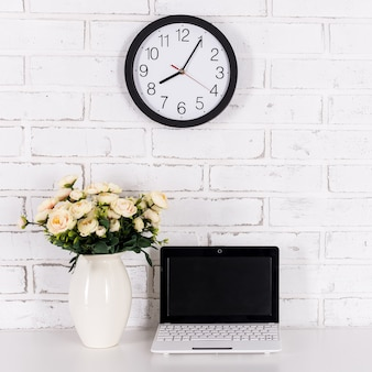 Workplace with modern laptop on the table at home or in office over white brick wall