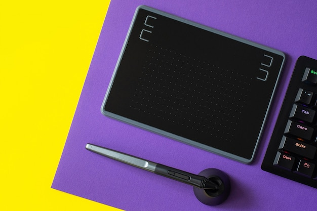 Workplace with notebook, pen graphics tablet, keyboard, on purple and yellow