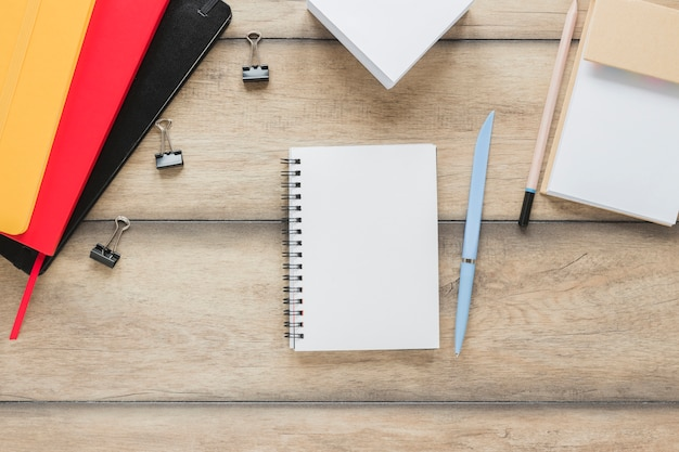 Workplace with notebook placed near stationery on wooden table