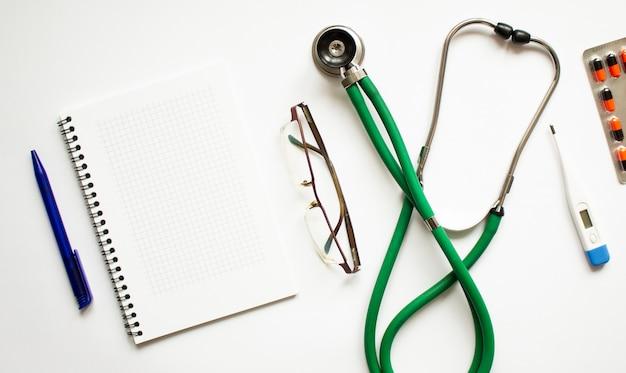 ノートブック聴診器の白いテーブルのある職場テキスト用のフラットレイスペース