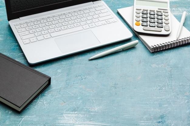 ノートブック、ラップトップ、電卓、ペンを備えた職場