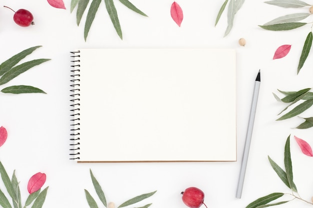 Workplace with a notepad mockup, pencil and floral frame on white table.