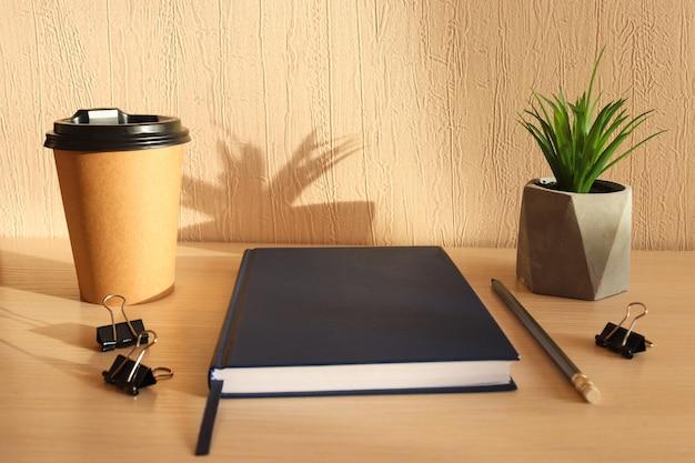 メモ帳、鉛筆、コーヒーカップ、植物のある職場