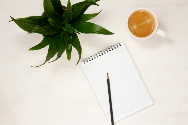 A workplace with a notepad, pencil, coffee cup and potted flower is placed on a white background. flat spoon, top view.