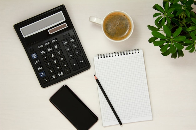 A workplace with a notepad, phone, pencil, calculator, coffee cup and potted flower is placed on a white background. flat spoon, top view.