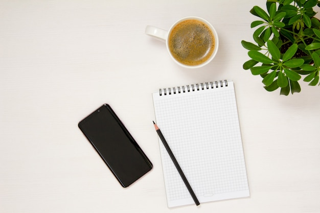 A workplace with a notepad, phone, pencil, coffee cup and potted flower is placed on a white background. flat spoon, top view.
