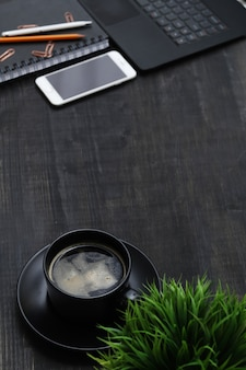 Workplace with smartphone, coffee cup, notebook, on black table. top view
