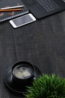 黒いテーブルの上のスマートフォン、コーヒーカップ、ノートブックと職場。上面図