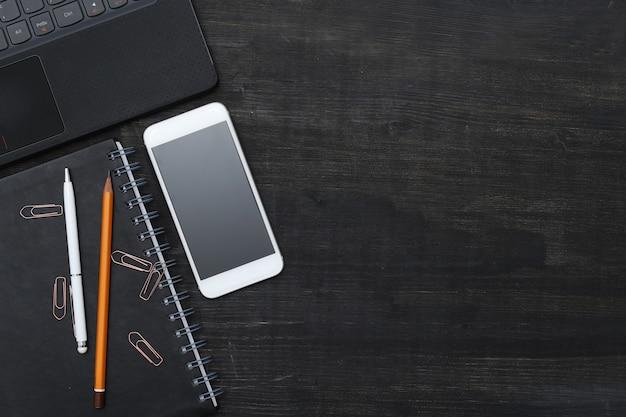 Рабочее место с смартфон, ноутбук, на черном столе. вид сверху
