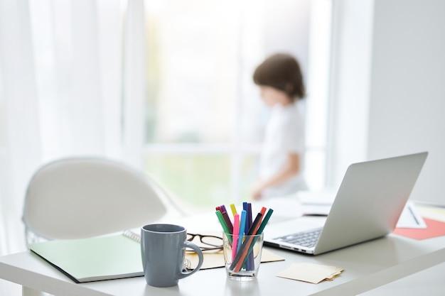 自宅のテーブルに白いノートパソコン、メモ、お茶を片手に職場。窓から差し込む明るい光。バックグラウンドで立っている小さな男の子。インテリアデザイン、家庭教育のコンセプト