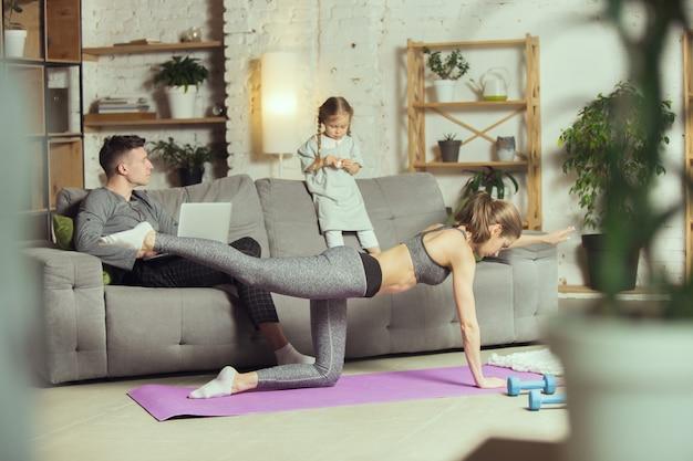 Allena le gambe. giovane donna che esercita fitness, aerobica, yoga a casa, stile di vita sportivo e palestra domestica. diventare attivi durante il lockdown, la quarantena. sanità, movimento, concetto di benessere.