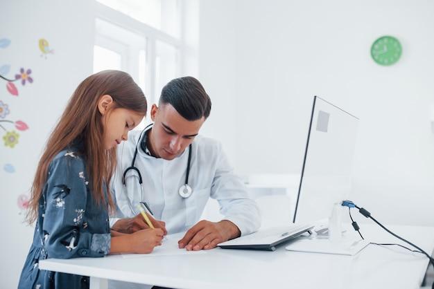 문서와 함께 작동합니다. 젊은 소아과 의사는 진료소에서 작은 여성 방문자와 함께 일합니다.