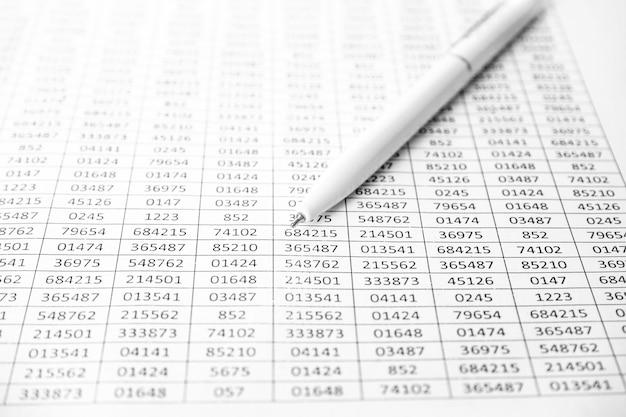 図と白いペンを示すワークシートまたはレポート。財務データにペン。会計。ビジネスと金融の研究の概念