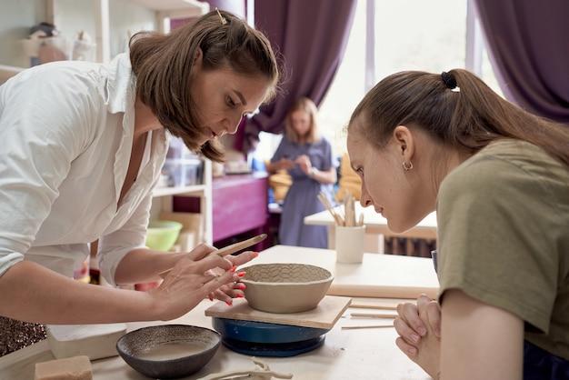 Мастер-класс по обучению гончарному делу, одна женщина учит другую