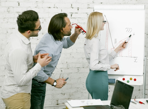 Workshop of businesswoman in office. blonde woman draws graphs and diagrams on a white board. male colleagues came closer to consider new information