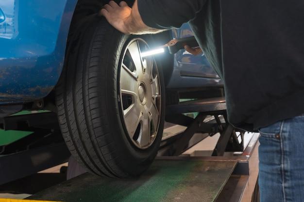 Осмотр автомобиля в мастерской, проверка с помощью фонарика на дефекты колеса, подвески и тормозов, ежегодный технический осмотр автомобиля.
