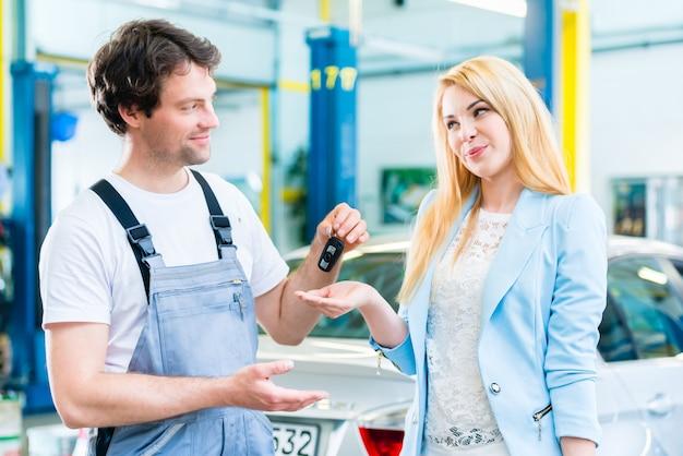 Workshop mechanic handing car to customer