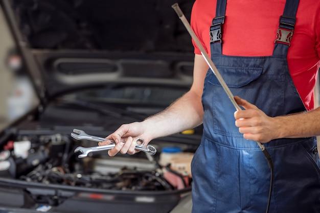 ワークショップ、ツール。ソケットレンチとランプが付いている車の開いたボンネットの近くに立っている自動車整備士の手