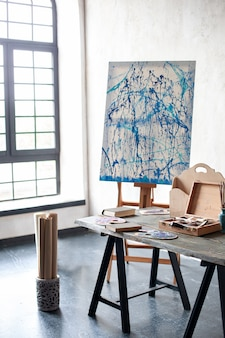 Workspace of the artist, no people. easel, canvases and brushes for teaching drawing. scandinavian interior, loft. the interior in the studio of the artist, workshop, hobbies. studio drawing, pencils