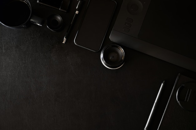 Workspace on black leather top table of a creative designer or photographer and copy space