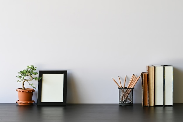 Workspace books, pencil, photo frame and bonsai on office desk.