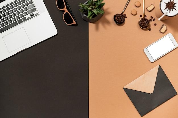 Плоский дизайн рабочей области для кофе с цифровым гаджетом и закрытым бумажным конвертом. ароматные бобы арабики, ноутбук, мобильный телефон, солнцезащитные очки, вид сверху растений.
