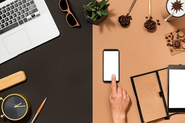 Workspace coffee design. hand point on mobile phone blank white screen. flat lay top view desk with stationery, arabica bean, digital device.