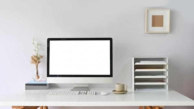 작업 공간 책상에 퍼 팅과 책장, 마우스, 키보드, 커피 컵 흰색 빈 화면이 컴퓨터 모니터.