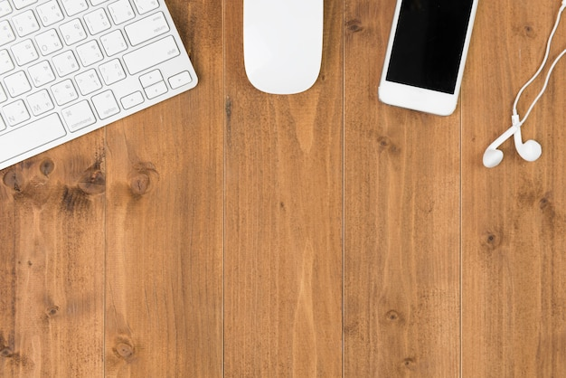 Workspace, computer and smartphone on wooden table, top view