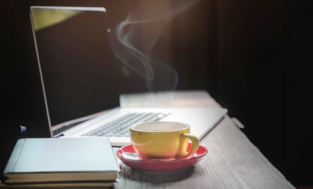 Workspace concept in dark tone color with laptop and cup of coffee on wooden table.