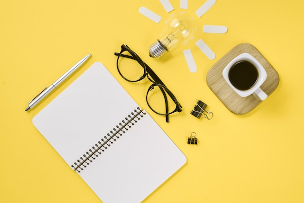 Workspace desk styled design office supplies with pen, notepad, eyeglasses, cup coffee and light bulb
