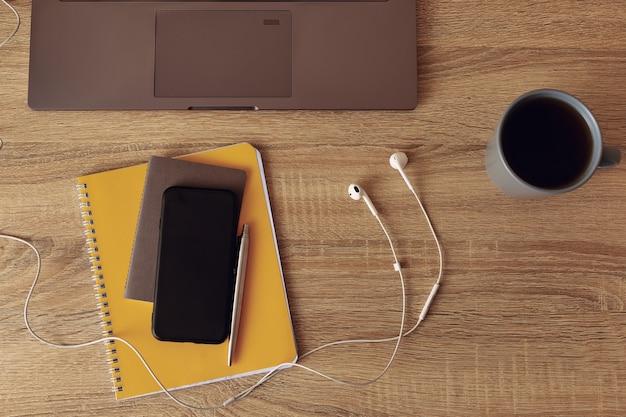 Рабочий стол. вид сверху на желтый блокнот с мобильным телефоном, белыми наушниками и частью ноутбука.