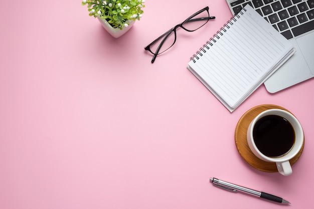 분홍색 배경에 커피 잔 키보드 안경 작업 공간 책상. 공간을 복사하십시오.