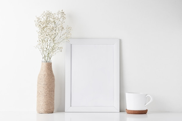 Workspace desk with empty frame and flower in vase