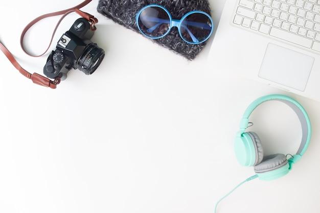 ラップトップコンピュータ、カメラ、ヘッドフォン、女性のアクセサリーを備えたワークスペースデスク Premium写真